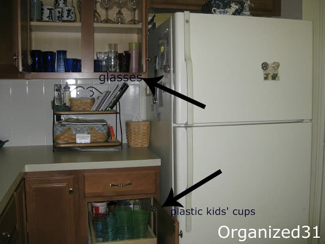 Kitchen cupboard next to refrigerator with arrow overlays.