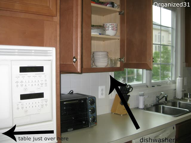 Cabinet above dishwasher with arrow overlay.