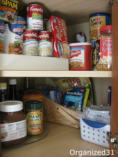 two organized cabinet shelves with cans and jars