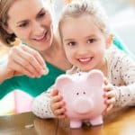 Mother and child with piggy bank and coins