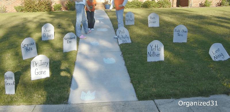 children standing on sidewalk with DIY Halloween tombstones in the yard