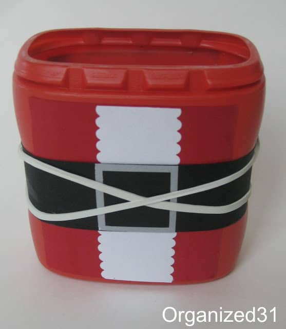 red plastic container decorated to look like Santa suit with rubber bands wrapped around it