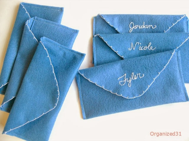 3 blue felt envelopes next to 3 with names embroidered in white