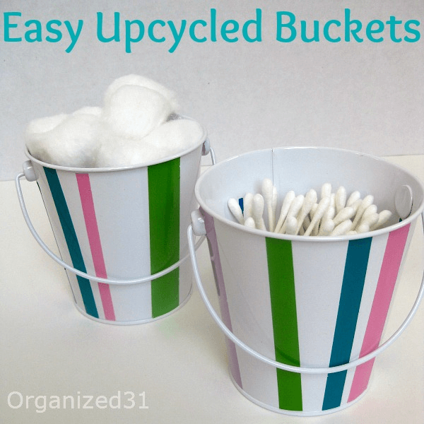 2 white and colorful striped buckets holding cotton swab and cotton balls