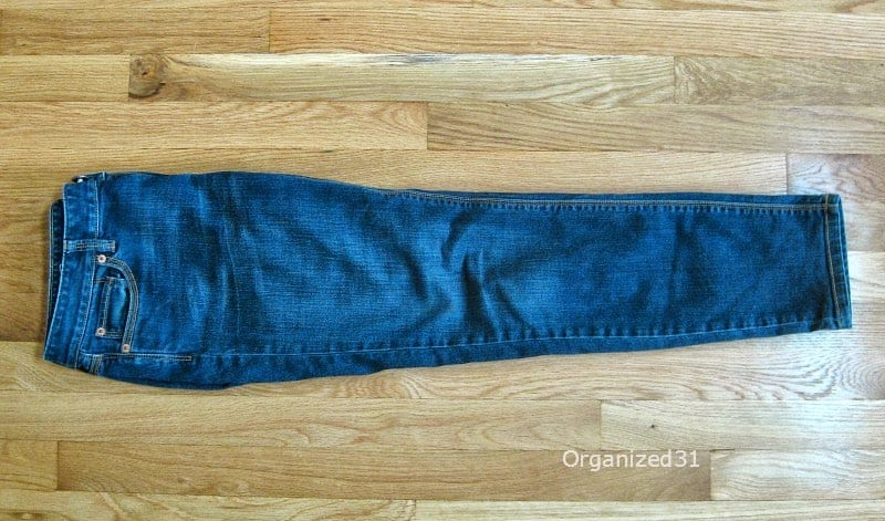 blue jeans folded length wise on wood table