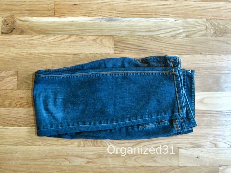 blue jeans folded in half and in half again on wood table