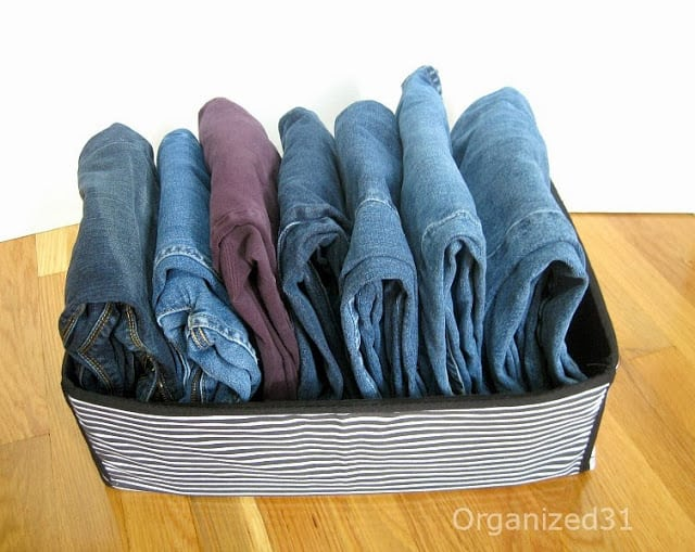 7 pairs of jeans neatly folded in a bin
