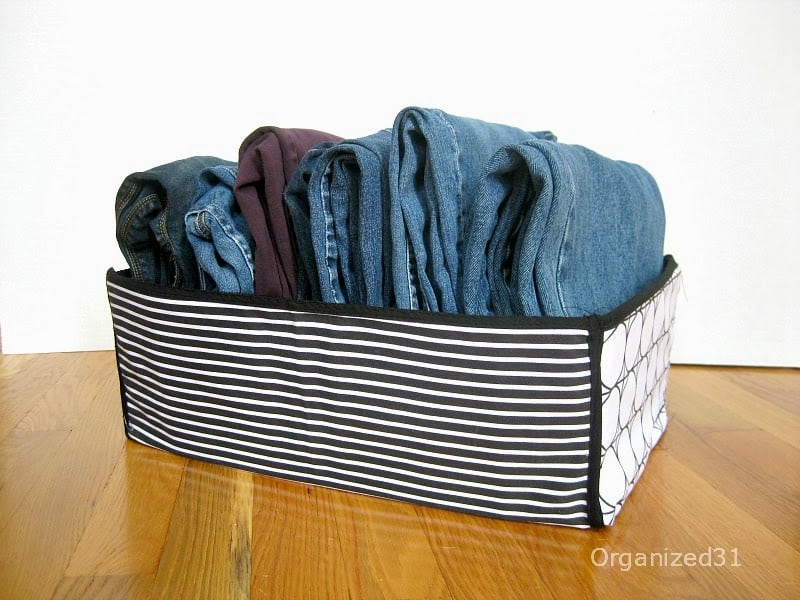 jeans folded neatly in striped box on wood table