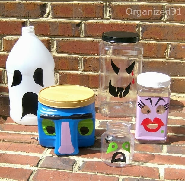 5 decorated plastic jars in front of brick wall