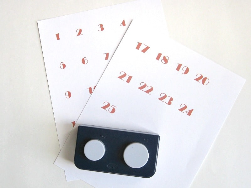 2 sheets of paper with red numbers 1 - 25 and hole punch