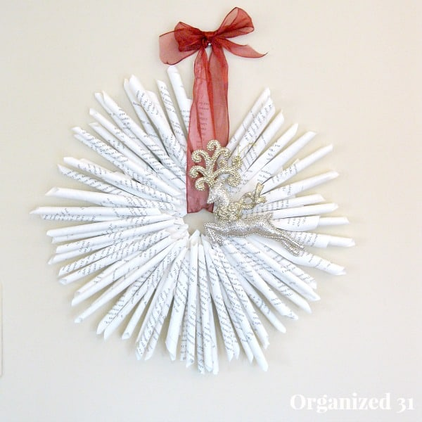Book Page Wreath hanging from a red ribbon
