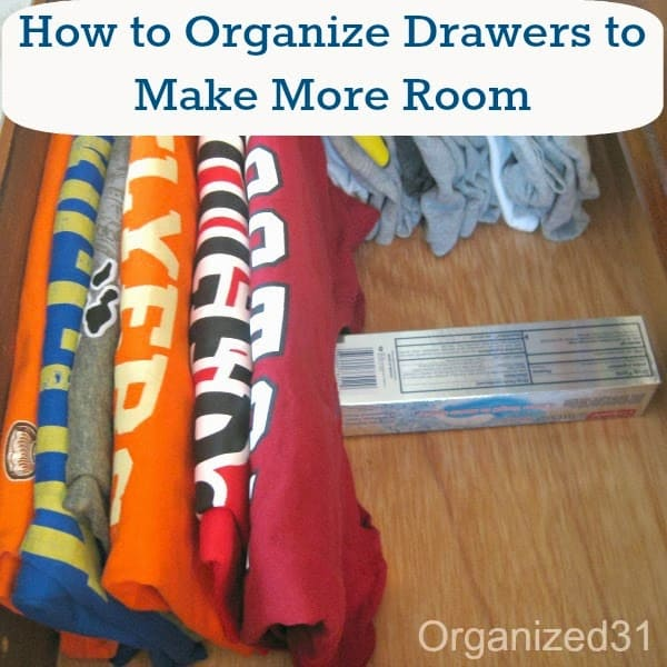 Folded t-shirts in drawer with box supporting them