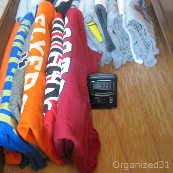 side view of t-shirts in drawer with alarm clock supporting the pile