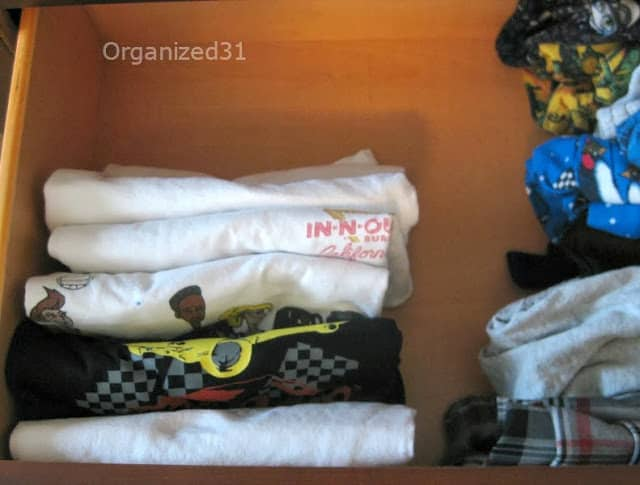 overhead view of shirts and pants filed folded in drawer