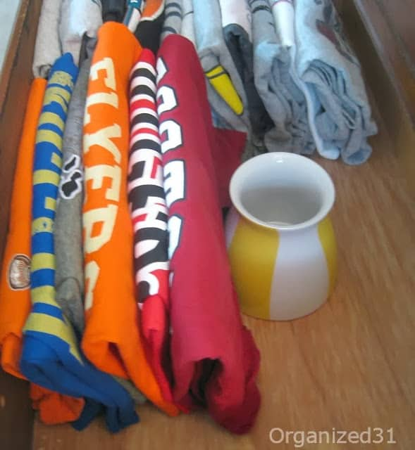 side view of folded t-shirts with vase supporting pile