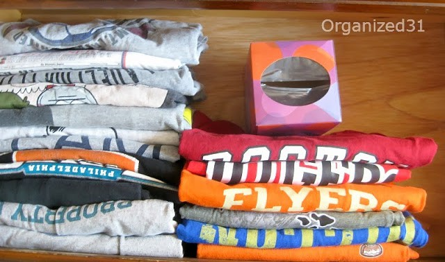 overhead view of file folded t-shirts with tissue box supporting t-shirts