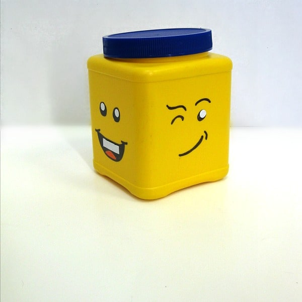 yellow can with different Lego faces on adjacent sides