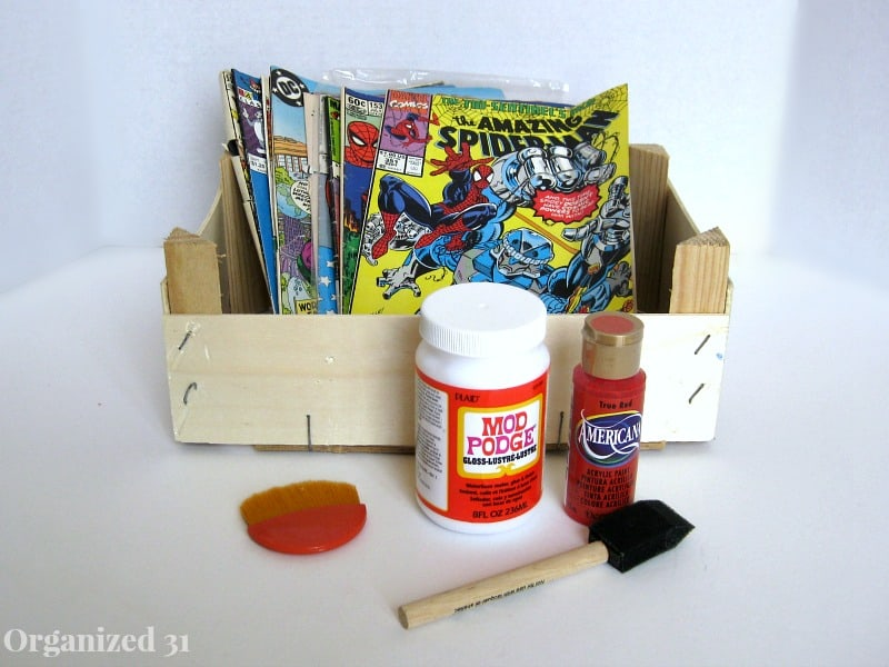 wood crate holding comic books with bottle of red paint, bottle of Mod Podge and sponge brush on table