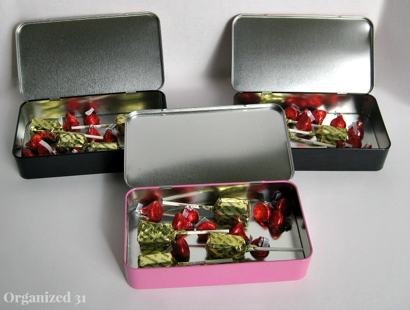 3 open pencil boxes holding candy