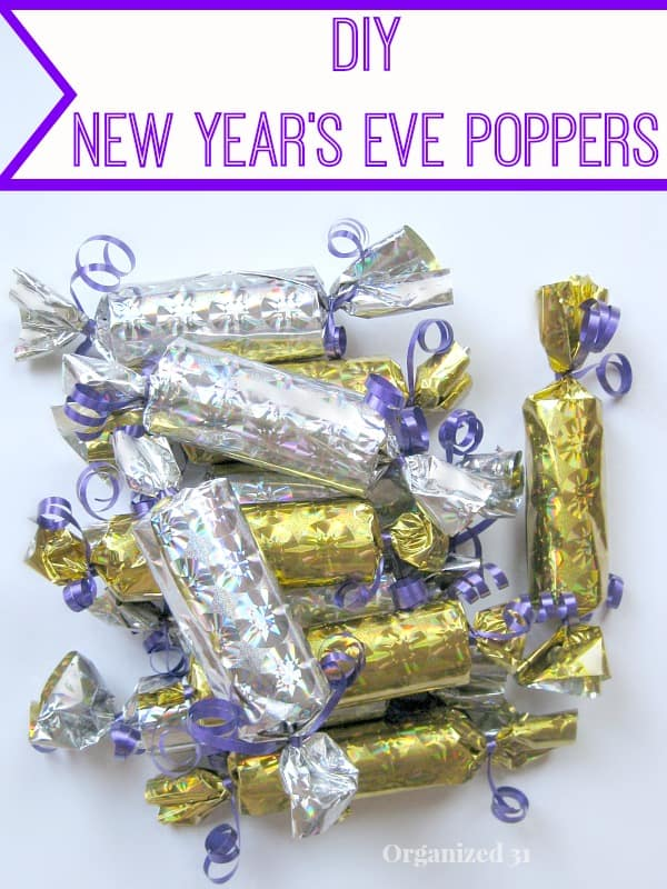 pile of silver and gold foil poppers with purple ribbon on white table