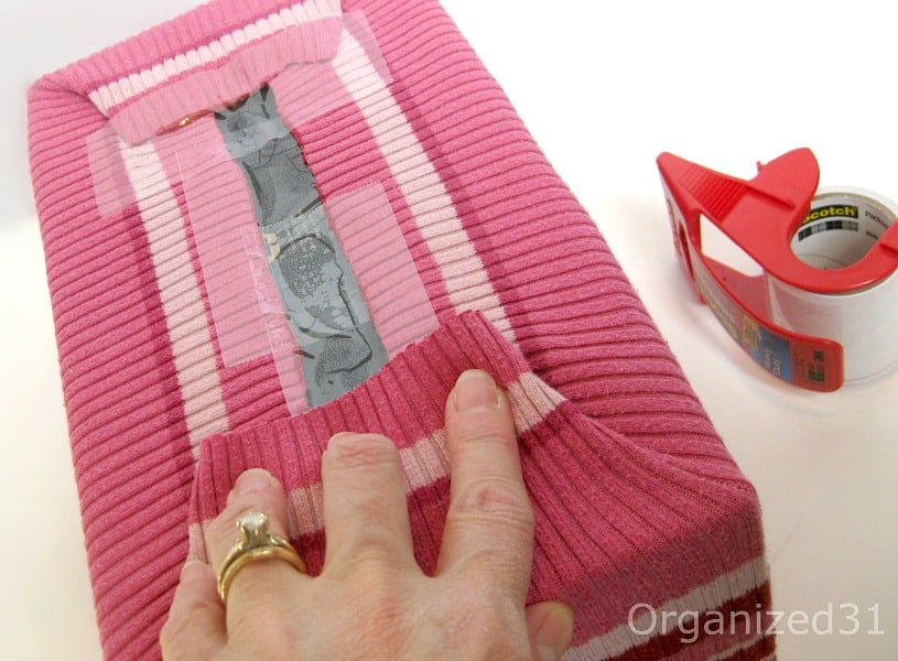 Pull the finished edge of the sweater hem into the inside of the box and down about an inch.  If your sweater has a pattern, line the pattern, make sure the pattern is straight all around the box.