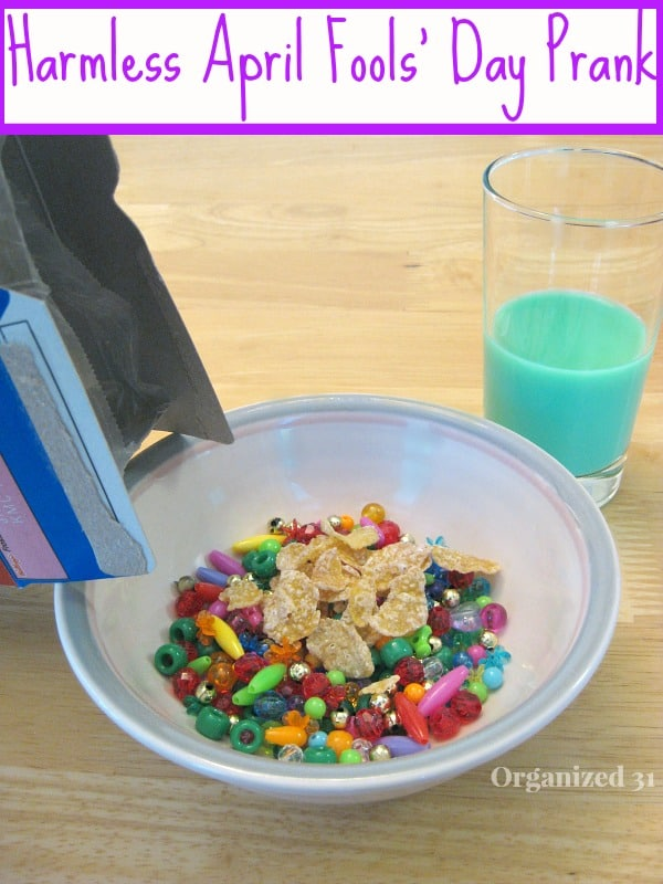 Box of cereal pouring cereal and beads into bowl with glass of green milk