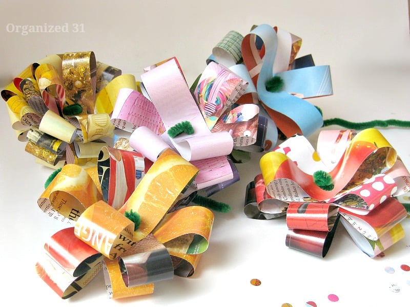side view of 5 colorful paper craft flowers on white table with paper punch circles scattered around