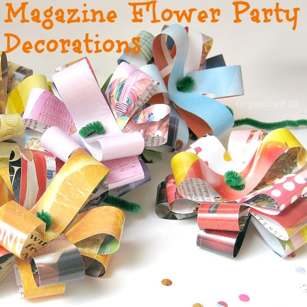 close up of colorful paper craft flowers on white table with hole punch circles on tab le