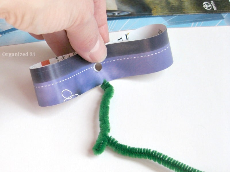 hand holding loop of paper with hole in middle next to green pipe cleaner