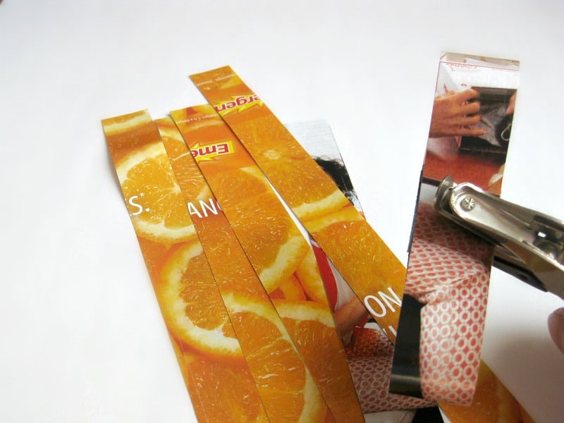 strips of orange colored paper and hole puncher with strip of paper