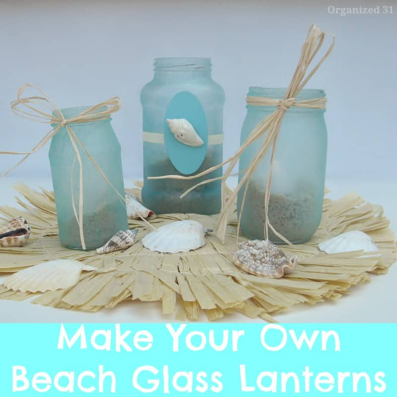 3 frosted glass jars with shells and raffia on raffia mat