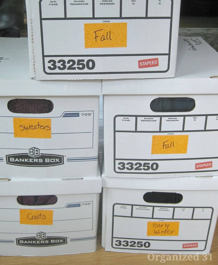 Stack of 5 white boxes with labels specifying categories of clothes packed in boxes