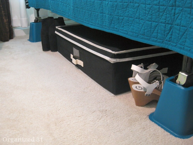 bed on blue bed risers with blue bedspread and black storage box under the bed