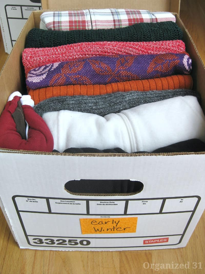 close up of white box with sweaters neatly folded and filed in the box
