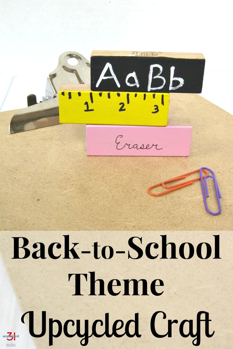 3 school themed decorated blocks stacked on a clipboard with 3 paperclips in foreground