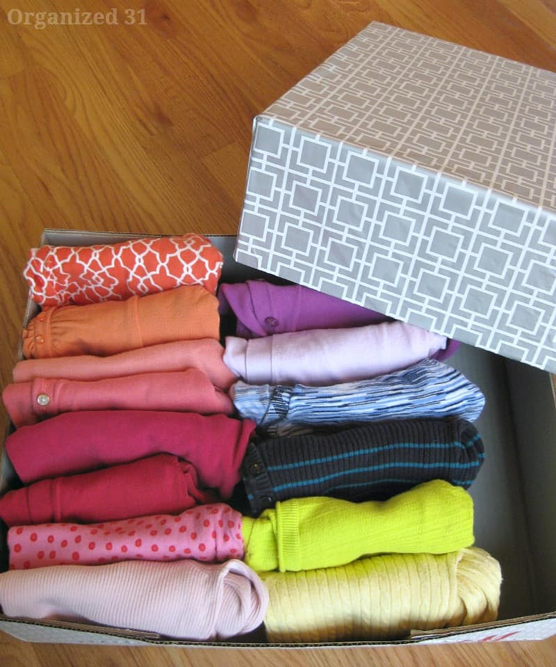 close up of neatly folded clothes in open box with decorated lid next to it