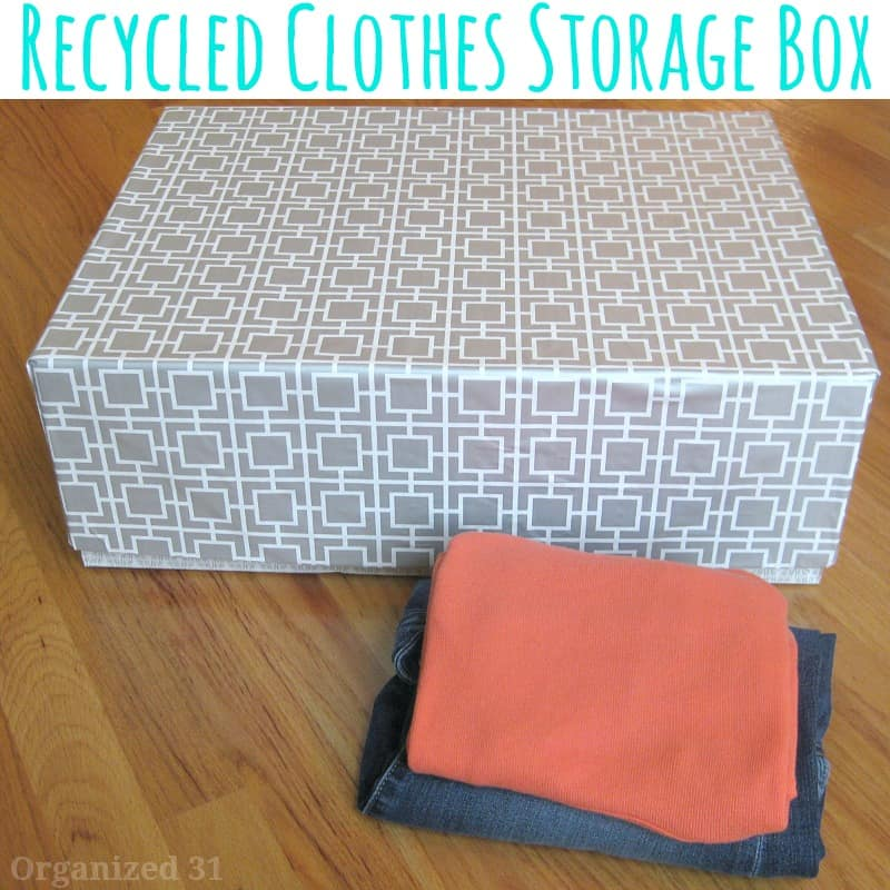 stack of clothes in front of decorated box on wood table with title text reading Recycled Clothes Storage Box