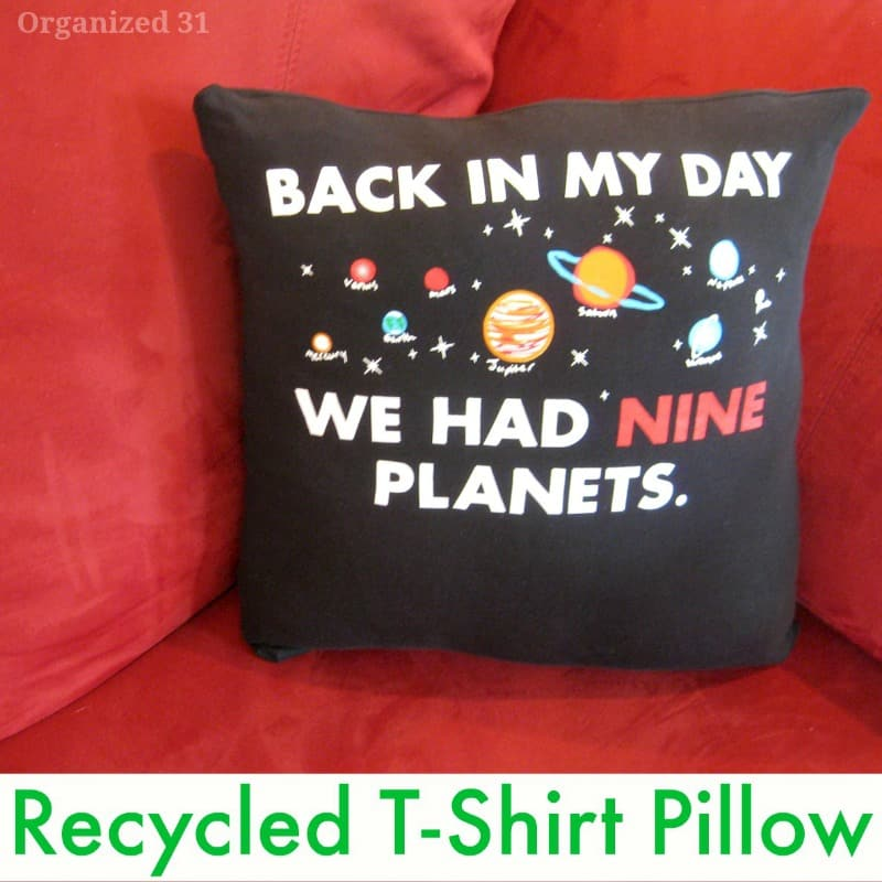 "black pillow that says ""Back in my day we had nine planets"" on a red couch"