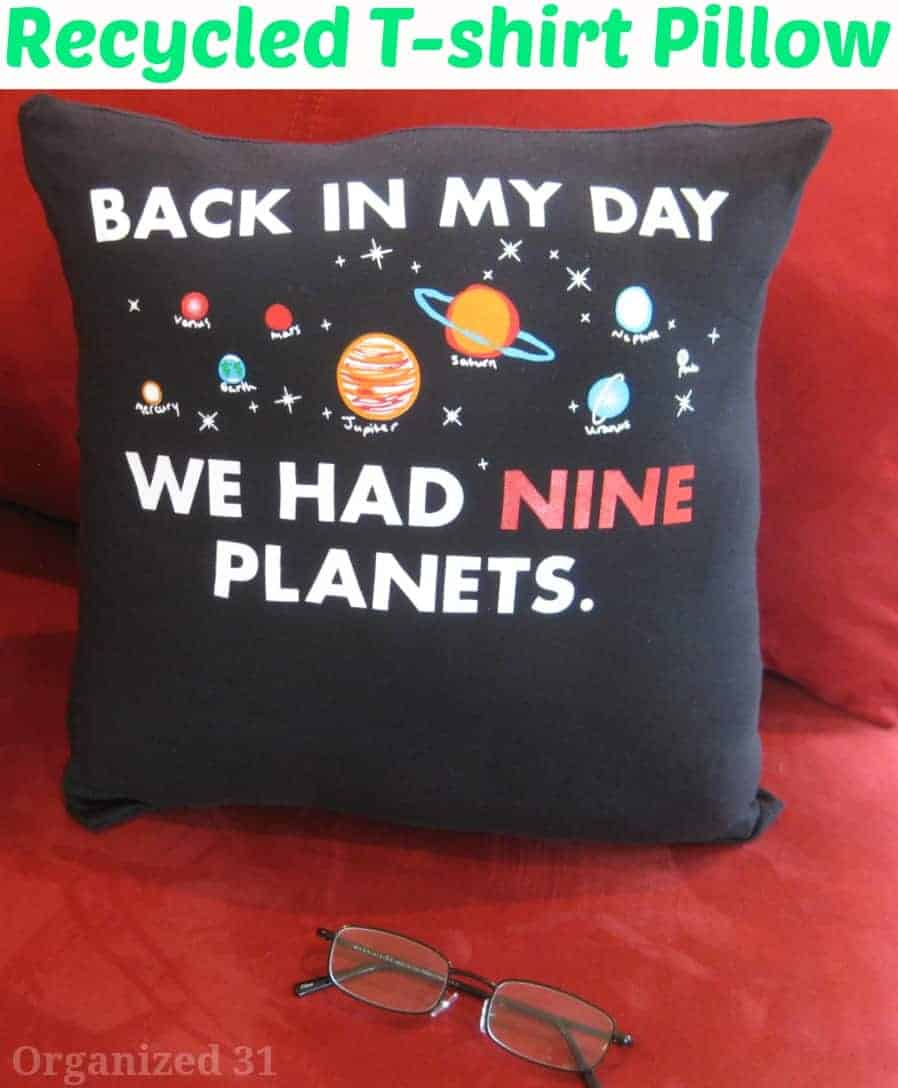"black pillow on red couch. Pillow says, ""Back in my day we had nine planets."" with reading glasses laying on couch."
