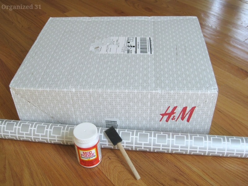shipping box, roll of grey and white wrapping paper, bottle of decoupage glue and sponge brush