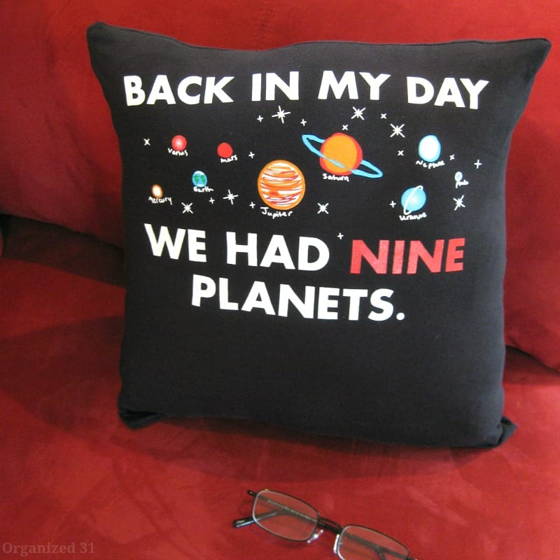black pillow made from t-shirt with planets on it sitting red couch with pair of glasses in foreground