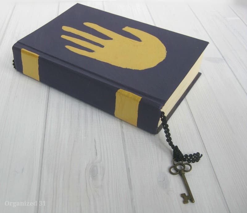 upcycled book cover with painted gold hand image and skeleton key bookmark