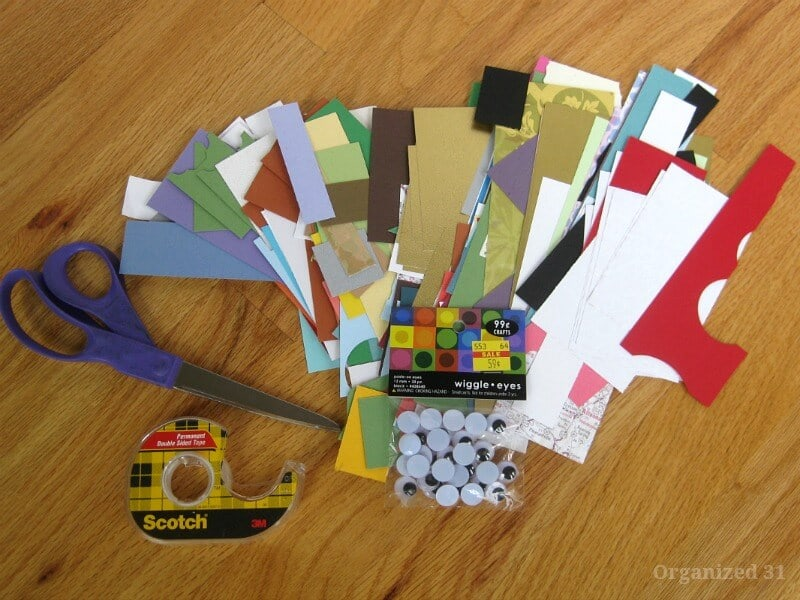 pile of colorful paper scraps, scissors, roll of tape and googly eyes on wood table