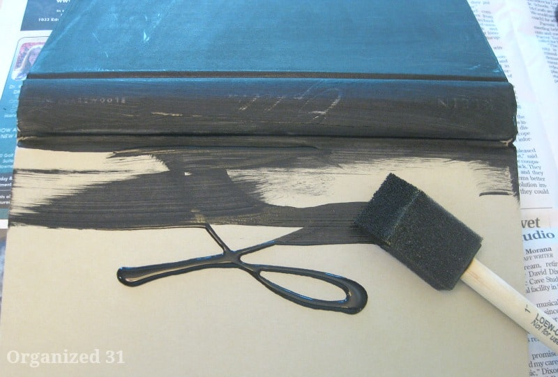 sponge brush adding black paint to the cover of a book