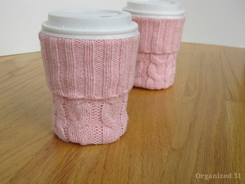 2 coffee cups with pink knit sleeves on wood table