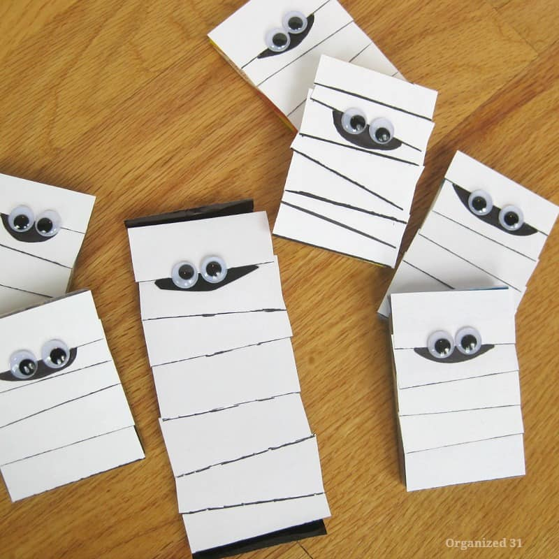 several paper crafted mummies with googly eyes scattered on wood table
