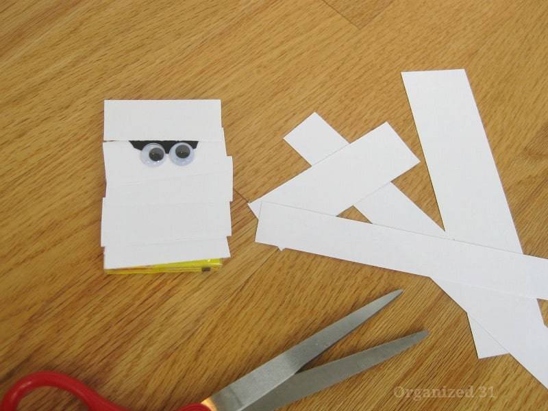 scissors, strips of white paper and paper crafted mummy on wood table