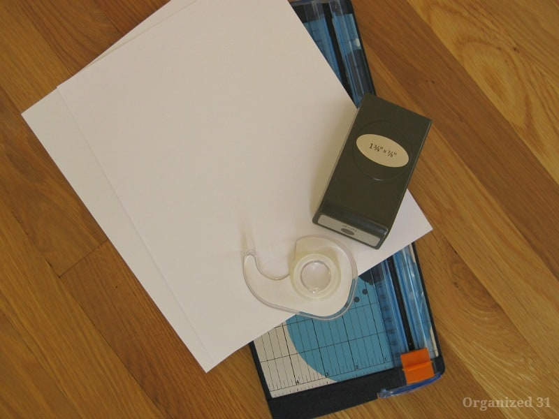 paper laying on top of blue paper cutter, with tape and oval punch