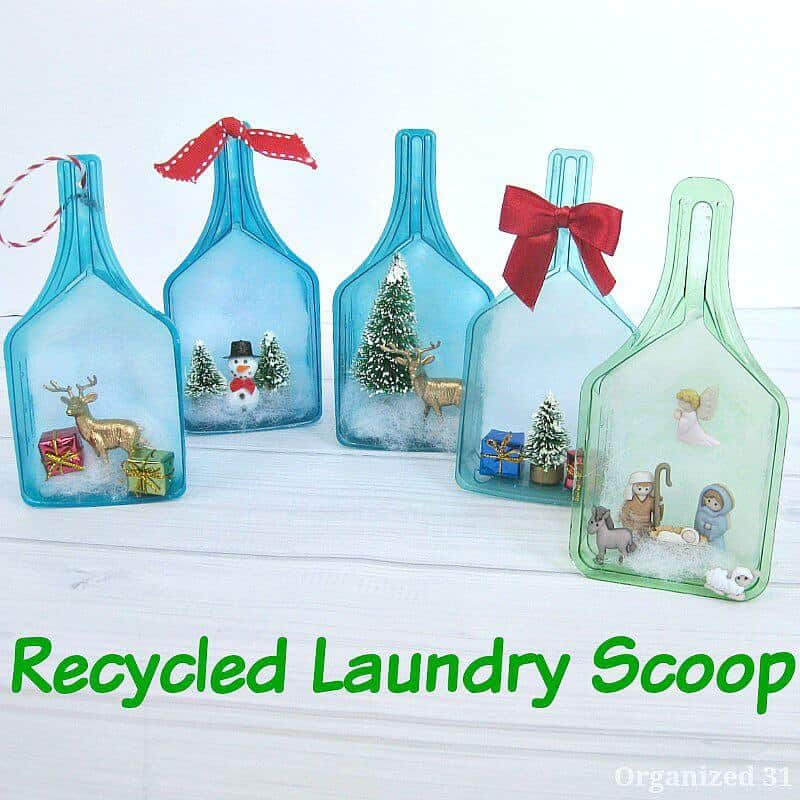 5 ornaments made from laundry scoops on white wood table