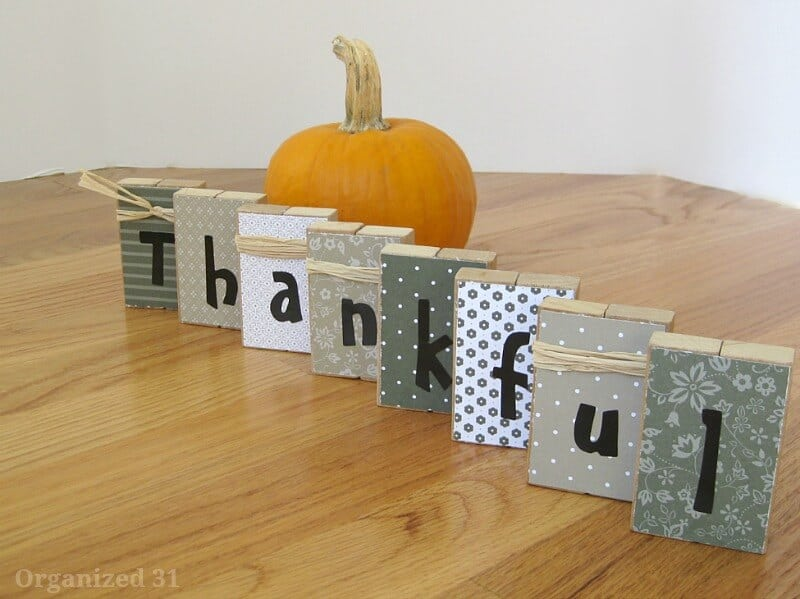 blocks decorated in neutral colors spelling thankful next to small pumpkin on wood table
